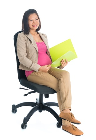 six months: Full body six months pregnant Asian businesswoman holding file folder document seated on chair, isolated on white background.