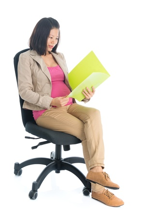 Full body six months pregnant Asian businesswoman reading file document sitting on chair, isolated on white background. photo