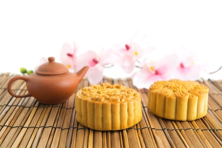 Traditional mooncakes on table setting with teapot. Chinese mid autumn festival foods. The Chinese words on the mooncakes means assorted fruits nuts and durian pure lotus paste, not a logo or trademark. Stock Photo