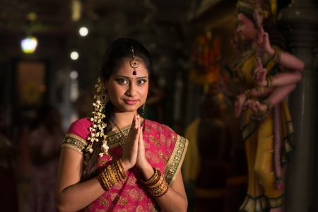 Young Indian girl in traditional sari dress praying in a hindu temple.