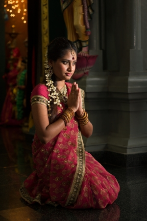 Young Indian woman in traditional sari dress praying in a hindu temple. photo