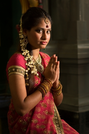 sari: Young Indian female in traditional sari dress praying in a hindu temple.