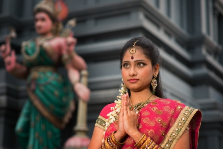 Beautiful young Indian woman in traditional sari dress praying in a hindu temple. photo