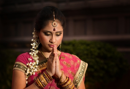 Portrait of beautiful young Indian woman in traditional sari dress praying in a hindu temple. photo
