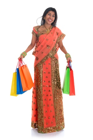 Portrait of full length beautiful traditional Indian woman in sari dress holding shopping bags, isolated over white background.  photo