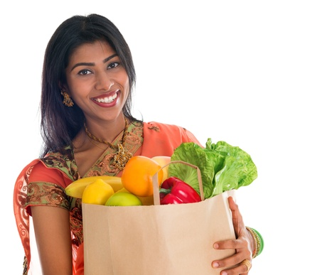 grocery bag: Happy grocery shopper. Portrait of beautiful traditional Indian woman in sari dress holding paper shopping bag full of groceries isolated on white.