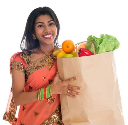 grocery shopping: Happy grocery shopper. Portrait of beautiful traditional Indian woman in sari dress holding paper shopping bag full of groceries isolated on white.