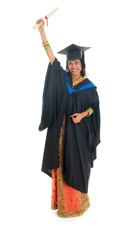 Full length happy Indian university student in graduation gown and cap holding diploma certificate. Portrait of mixed race Asian Indian and African American female model standing isolated on white background. photo