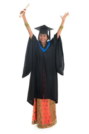 Full length arms up Indian university student in graduation gown and cap holding diploma certificate. Portrait of mixed race Asian Indian and African American female model standing isolated on white background. photo