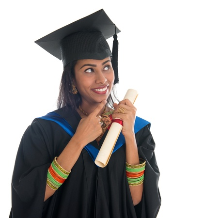 Happy Indian university student in graduation gown and cap holding diploma certificate thinking. Portrait of mixed race Asian Indian and African American female model standing isolated on white background. photo