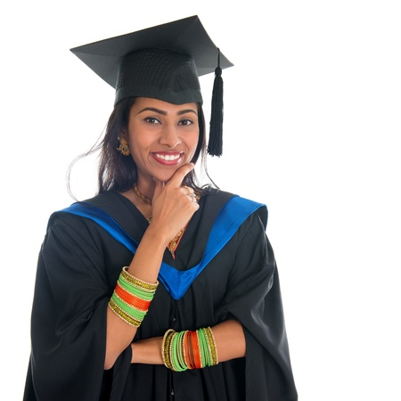 Happy Indian university student in graduation gown and cap thinking. Portrait of mixed race Asian Indian and African American female model standing isolated on white background. photo