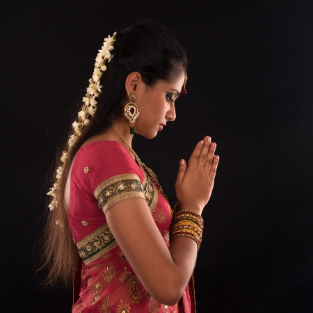 saree: Portrait of beautiful young Indian woman prayer in traditional sari dress, isolated on black background. Stock Photo