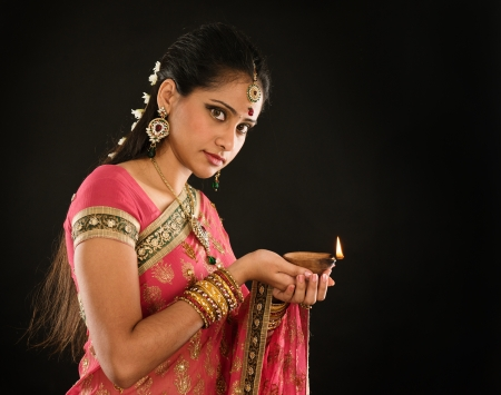 Portrait of beautiful young Indian woman in traditional sari dress holding diwali oil lamp light, isolated on black background. photo
