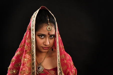 Head shot of beautiful young Indian woman in traditional sari dress, veil covering head, isolated on black background. Stock Photo