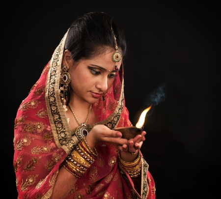 Beautiful young Indian woman in traditional sari dress holding a diwali oil lamp light, isolated on black background.