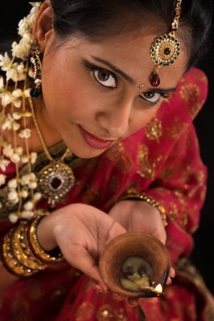 ethnic festival: Close up portrait of beautiful young Indian woman in traditional sari dress holding a diwali oil lamp light, isolated on black background.