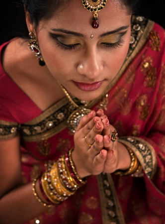 Close up portrait of beautiful young Indian woman prayer in traditional sari dress, isolated on black background. photo