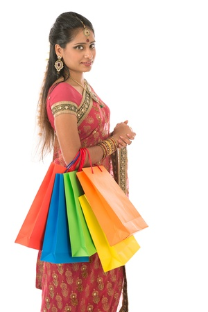 Portrait of beautiful young Indian woman shopper in traditional sari dress, standing isolated on white background. photo