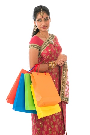 Beautiful young Indian woman in traditional sari dress having diwali shopping, standing isolated on white background. photo