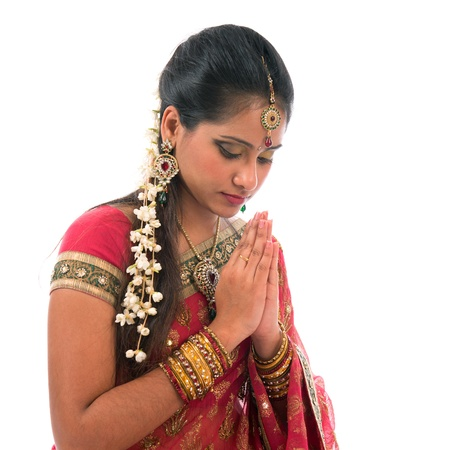 Portrait of beautiful young Indian woman prayer in traditional sari dress, isolated on white background.