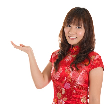 qipao: Pretty Asian woman with Chinese traditional dress cheongsam or qipao hand showing blank space. Chinese new year concept, female model isolated on white background.