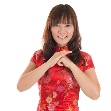 chinese dress: Asian woman with Chinese traditional dress cheongsam or qipao greeting. Chinese new year concept, female model isolated on white background.
