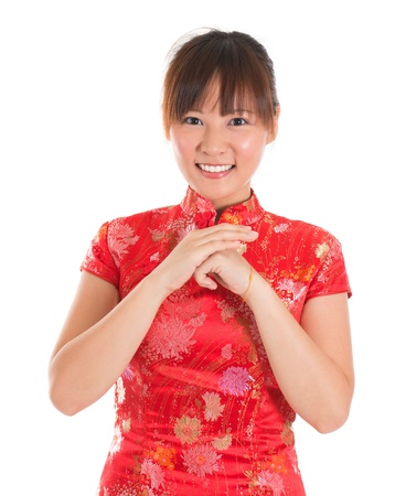 respecting: Asian woman with Chinese traditional dress cheongsam or qipao respecting on Chinese New Year Festival. Female model isolated on white background.