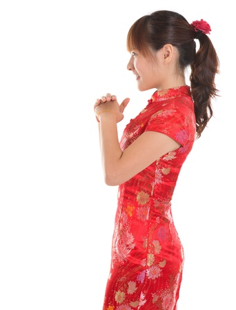 respecting: Side view Asian woman with Chinese traditional dress cheongsam or qipao respecting on Chinese New Year Festival. Female model isolated on white background. Stock Photo