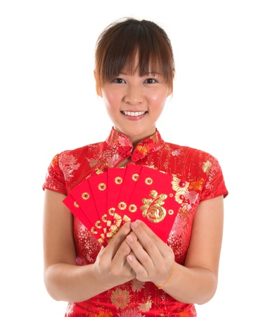 Pretty Asian woman with Chinese traditional dress cheongsam or qipao holding ang pow or red packet monetary gift. Chinese new year concept, female model isolated on white background. photo
