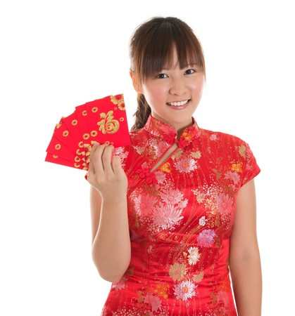 ang: Pretty Asian girl with Chinese traditional dress cheongsam or qipao holding ang pow or red packet monetary gift. Chinese new year concept, female model isolated on white background.