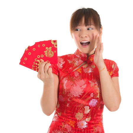 Asian woman with Chinese traditional dress cheongsam or qipao holding ang pow or red packet monetary gift showing surprise face expression. Chinese new year concept, female model isolated on white background.