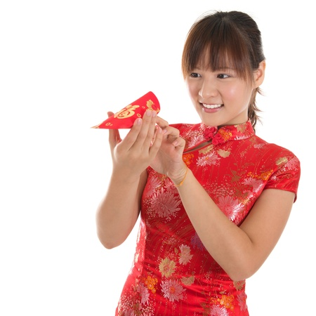 Asian woman with Chinese traditional dress cheongsam or qipao holding ang pow monetary gift, peeking into red packet. Chinese new year concept, female model isolated on white background. photo