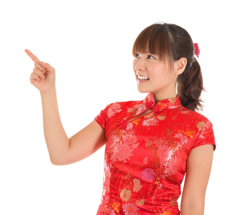 qipao: Pretty Asian woman with Chinese traditional dress cheongsam or qipao finger pointing at blank copy space. Chinese new year concept, female model isolated on white background.