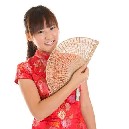 traditional clothes: Asian woman with Chinese traditional dress cheongsam or qipao holding Chinese fan. Chinese new year concept, female model isolated on white background. Stock Photo