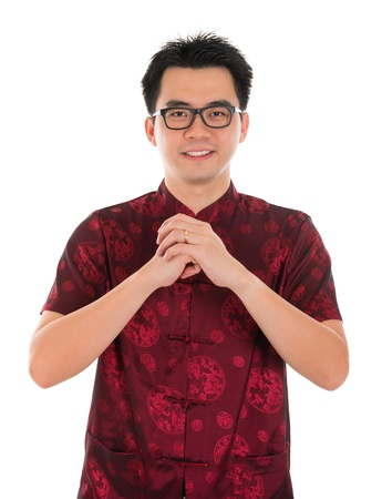 tang: Asian man with Chinese traditional dress cheongsam or tang suit greeting. Chinese new year concept, male model isolated on white background.