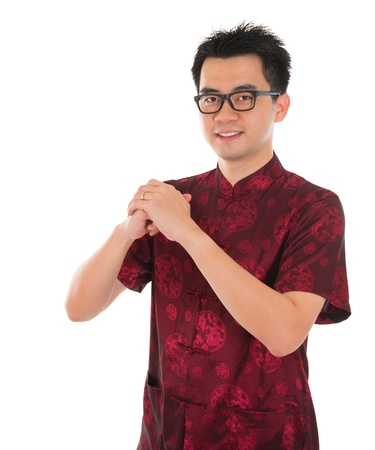 Asian male with Chinese traditional dress cheongsam or tang suit greeting. Chinese new year concept, male model isolated on white background. Stock Photo - 21893202