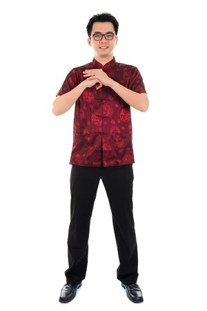 tang: Full body Asian man with Chinese traditional dress cheongsam or tang suit greeting. Chinese new year concept, male model isolated on white background. Stock Photo