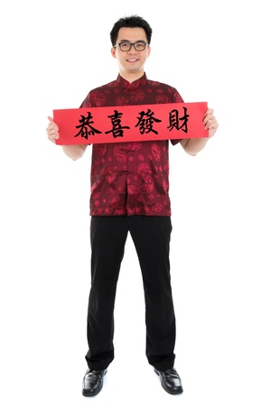 tang: Full body Asian man with Chinese traditional cheongsam or tang suit holding couplet, the Chinese word means congratulations and best wishes for a prosperous New Year.  Male model isolated on white background.