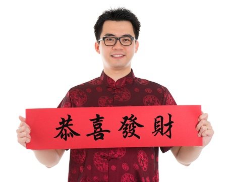 tang: Asian man with Chinese traditional cheongsam or tang suit holding couplet, the Chinese word means congratulations and best wishes for a prosperous New Year.  Male model isolated on white background.
