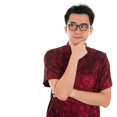 tang: Asian man with Chinese traditional cheongsam or tang suit having a thought.  Male model isolated on white background.