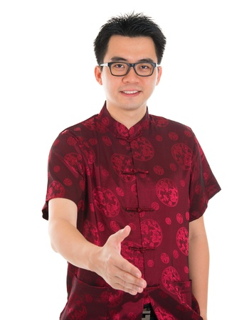 Asian man in traditional Chinese Cheongsam or Tang suit extending hand to give a handshake, standing isolated on white background. Asian male model. photo