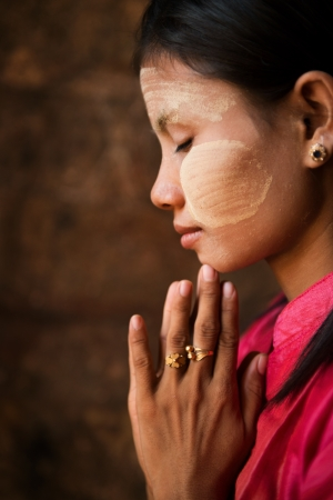 Beautiful traditional Myanmar girl is praying inside temple. photo