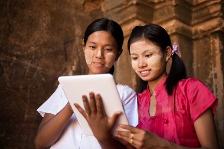 myanmar: Portrait of two beautiful young traditional Myanmar girl using digital tablet pc together.