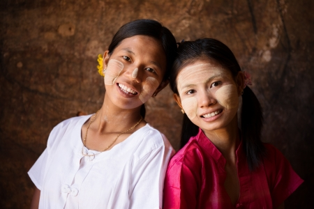 Portrait of two beautiful young traditional Myanmar girls smiling together. photo