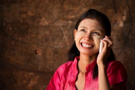 burmese: Portrait of beautiful young traditional Myanmar girl using smart phone.