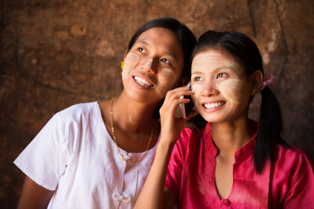 Portrait of two beautiful young traditional Myanmar girls using smart phone. Stock Photo - 22112474
