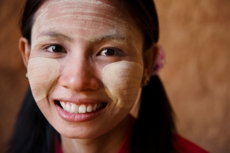 Portrait of beautiful young traditional Myanmar girl smiling. Close up head shot. photo