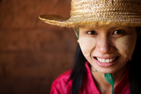 Portrait of beautiful young traditional Myanmar girl with straw hat smiling. Close up head shot. photo