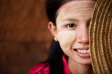 Portrait of beautiful shy young traditional Myanmar girl with straw hat smiling. Close up head shot. photo
