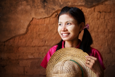 bagan: Portrait of beautiful young traditional Myanmar girl with straw hat looking away.